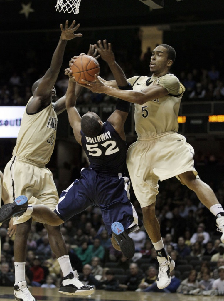 Tu Holloway of Xavier is fouled by Vanderbilt's Lance Goulbourne, right, as Steve Tchiengang also defends during Monday's game in Nashville, Tenn. Holloway made a pair of 3-pointers in overtime to propel Xavier to an 82-70 win.