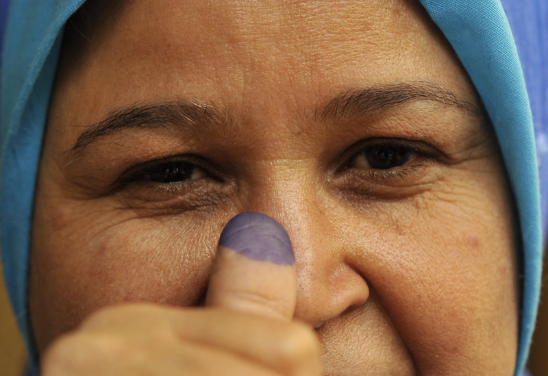 An Egyptian woman shows her inked finger after voting on Monday. Female voters appeared to outnumber men.