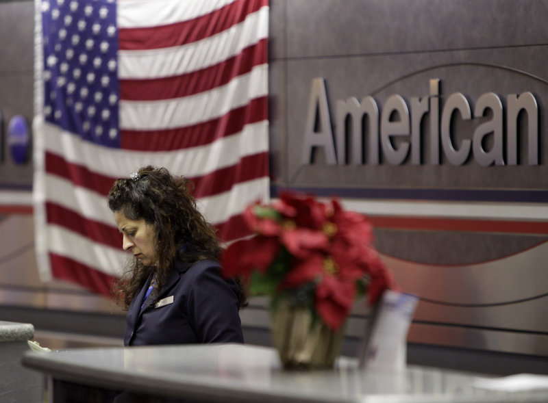 "An employee works at an American Airlines counter at LaGuardia Airport in New York on Tuesday. A consultant for the major airlines said, ""Labor is going to take a big hit"" as the carrier seeks to reduce costs in bankruptcy."