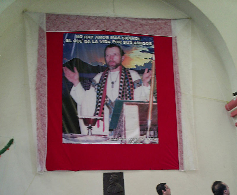 """A photograph of the Rev. Stanley Rother is displayed inside the church he served in remote Santiago Atitlan, Guatemala. Atop the photo are the words, """"There is no greater love than to give your life for your friends."""""""