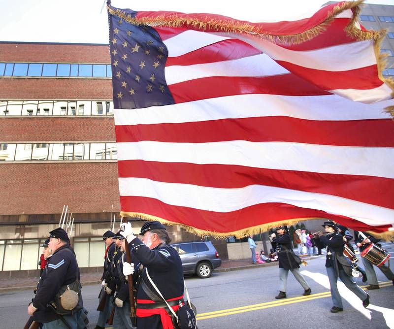 Larry Williams of Harpswell, a member of the 3rd Maine Regiment Volunteer Infantry, carriers an American flag during last year's Veteran's Day Parade down Congress Street in Portland.