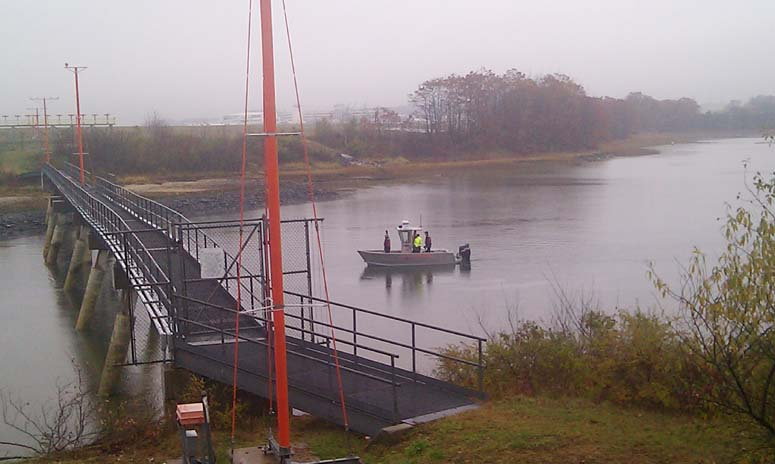 Emergency personnel monitor a fuel spill into the Fore River today.