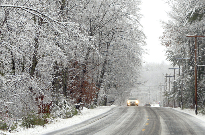 A car makes its way through the snow along Route 117 in Hollis today.