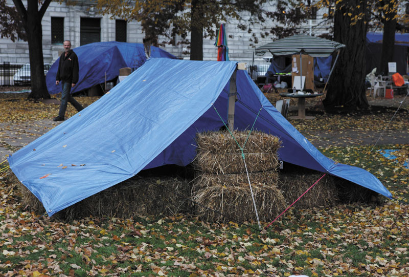 A pedestrian passes an Occupy Maine protester's tent insulated with hay bales on Tuesday on Nov. 15 in Portland.