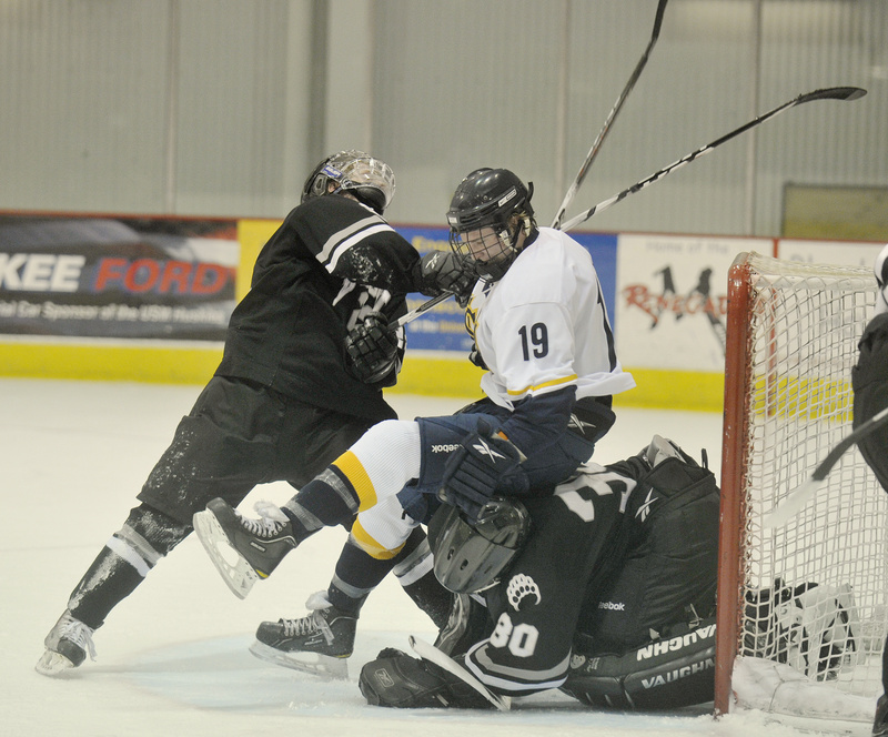 Mike Greene of the University of Southern Maine finds himself sandwiched by Nick Wetzel, left, and Bowdoin goalie Richard Nerland, who covers the puck in the crease Tuesday night during USM's 3-1 victory. The Huskies have won three straight following a 1-4 start to the season.
