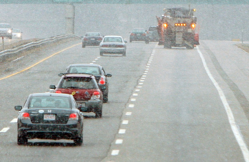 Gregory Rec/Staff Photographer: In a heavy snow squall, a plow truck patrols the northbound lane of the Maine Turnpike in Biddeford on Saturday. Snow and freezing temperatures made roads icy on Saturday morning sending cars off roads and causing numerous fender benders.