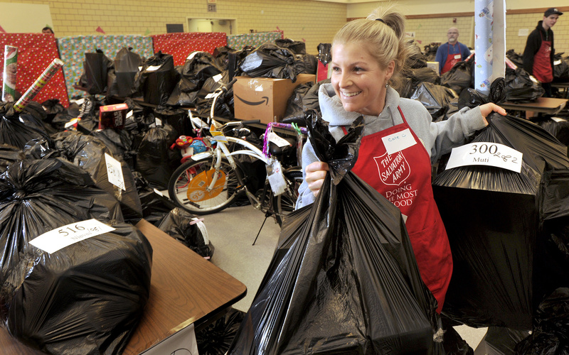 Salvation Army volunteer Cate Rust carries toy-filled bags out to waiting families Tuesday morning.