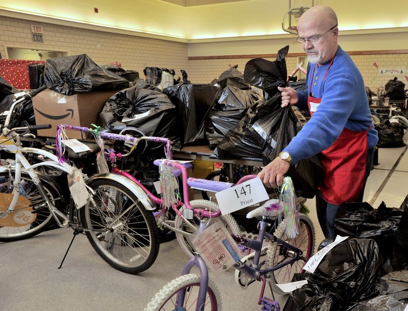 Volunteer Bob Parshley wheels out a bike along with another bag of toys to a waiting family Tuesday morning.