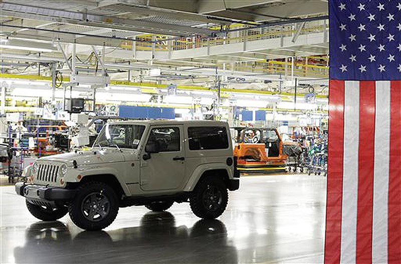 FILE - In this June 3, 2011 file photo, a 2012 Jeep Wrangler is shown next to the assembly line at Chrysler Group's Toledo Assembly complex, in Toledo, Ohio. Chrysler said Thursday, Dec. 1, 2011, its U.S. sales jumped 45 percent last month thanks to strong demand for the Jeep brand. (AP Photo/Paul Sancya, File)