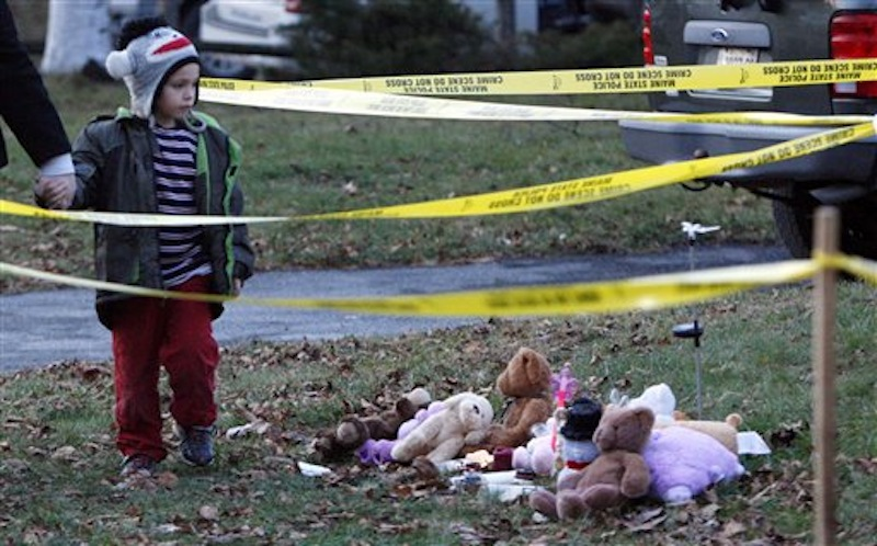 Isaiah Vear, 5, of Waterville, leaves a memorial after placing a toy for missing 20-month-old Ayla Reynolds outside the toddler's home, Thursday, Dec. 22, 2011. Investigators put up crime scene tape around the house on Thursday. (AP Photo/Robert F. Bukaty)
