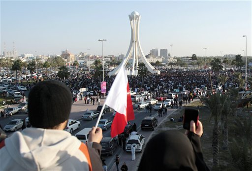 Bahrainis wave a flag and take photographs of protestors from a highway overpass overlooking the Pearl Monument centered on a main square in Manama, Bahrain, Tuesday Feb. 15, 2011.
