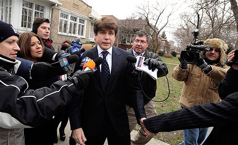 Former Illinois Governor Rod Blagojevich talks with the media while wife Patti leads him away as they leave their home heading to federal court for his sentencing hearing in Chicago, Tuesday, Dec. 6, 2011. Blagojevich was convicted earlier this year on 18 corruption counts, including trying to auction off President Barack Obama's old U.S. Senate seat. (AP Photo/Paul Beaty)