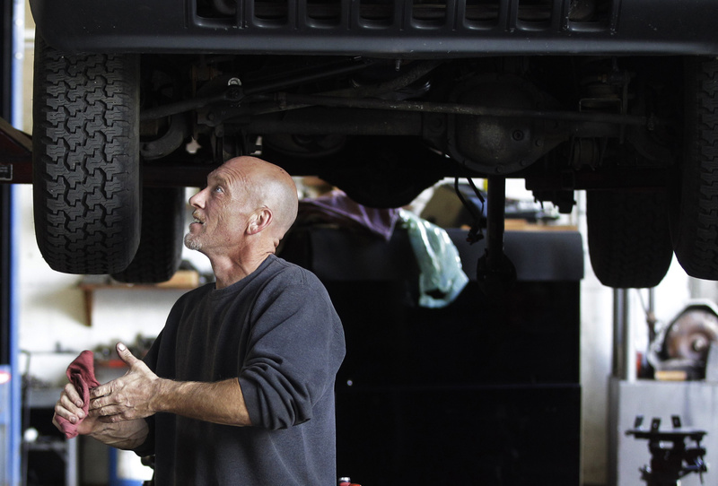 Bruce Worswick wipes his hands while working under a Jeep on the lift at Tri Town Transmission in Pembroke, Mass., on Oct. 4. U.S. service companies, which employ 90 percent of the country's work force, expanded at slower pace in November, and a measure of employment fell sharply.