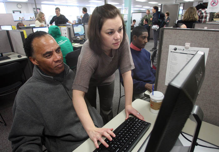 Maria Aplington, from United Parcel Service, helps Craig Wooten navigate their website during a hiring event for UPS at in Portland, Ore. The unemployment rate fell last month to its lowest level in more than two and a half years, as employers stepped up hiring in response to the slowly improving economy.