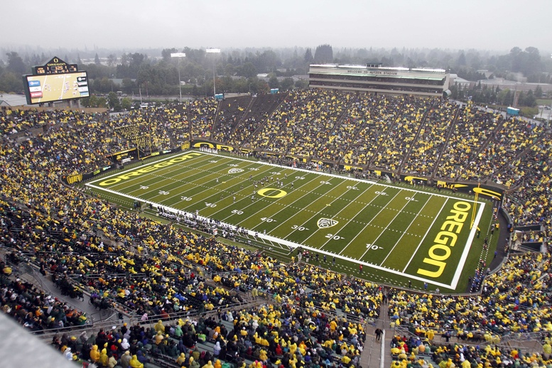 Spectators fill the University of Oregon's Autzen Stadium during an NCAA college football game. When the college football team was racking up wins on the field, the men in classrooms partied so hard their grades took a dive, a study finds.