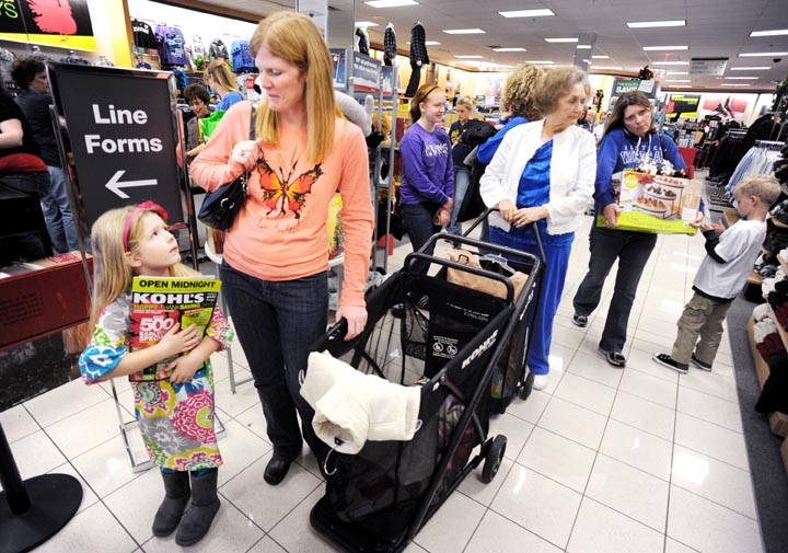 Emma Howe, left, looks up at her mother, Laurie Howe, as they wait in line at a Kohl's store in Owensboro, Ky., recently.