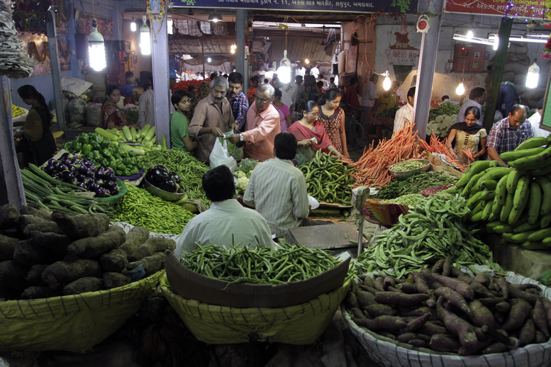 Indians shop for vegetables at a market in Ahmadabad, India, last month. A proposed open-door policy for foreign retailers may be put on hold.