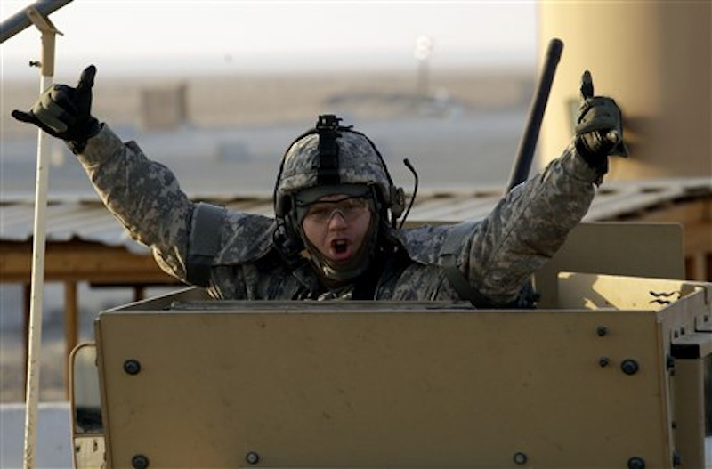 A soldier gestures from the gun turret of the last vehicle in a convoy of the US Army's 3rd Brigade, 1st Cavalry Division crosses the border from Iraq into Kuwait, Sunday, Dec. 18, 2011. The brigade's special troops battalion are the last American soldiers to leave Iraq. (AP Photo/Maya Alleruzzo)