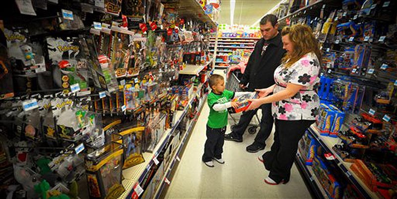 Kevin, center, Jolie, right, and Alex Lewis shop for a family they adopted for Christmas, Thursday Dec 15, 2011 at a Kmart in Omaha, Neb. The Lewises had their layaway paid off at Kmart by an unknown good Samaritan. (AP Photo/Dave Weaver)