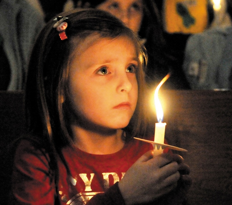 Katy Taylor, 5, joins in a vigil at the First Congregational Church in Waterville on Wednesday night for 20-month-old Ayla Reynolds, who was last seen Friday night and remains missing.