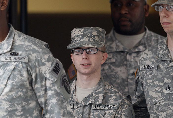 Army Pfc. Bradley Manning, center, is escorted out of a courthouse in Fort Meade, Md., today after a military hearing that will determine if he should face court-martial for his alleged role in the WikiLeaks classified leaks case.