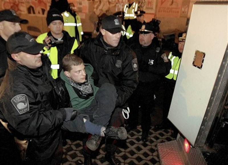Boston police officers escort an Occupy Boston protester to a police van at Dewey Square in Boston before dawn Saturday, Dec. 10, 2011. More than 40 people were peacefully arrested as the park was cleared. The city had set a Thursday midnight deadline for protesters to leave or face eviction. (AP Photo/The Boston Globe, Essdras M Suarez, , Pool)