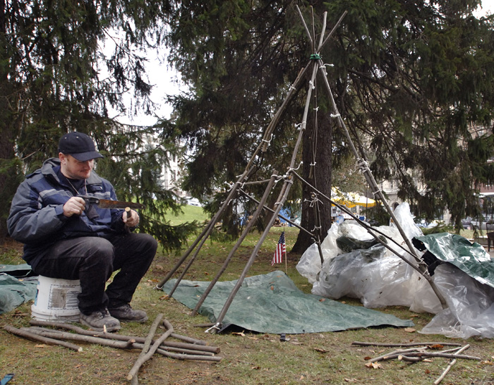 'Aaron' works on making himself a 'teepee' style dwelling at the The Occupy Bangor site in front of Pierce Park and the Bangor Public Library on Harlow Street in this Nov 17, 2011, photo.