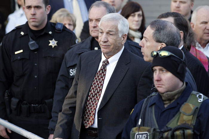 Jerry Sandusky, center, the former Penn State assistant football coach charged with sexually abusing boys, pauses as his attorney Joe Amendola, right, makes a point as they depart the Centre County Courthouse on Dec. 13, 2011, in Bellefonte, Pa.