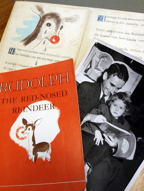 "A first edition of ""Rudolph, the Red-Nosed Reindeer,"" left, a photo of Robert May with his daughter, Barbara, right, and an original layout."