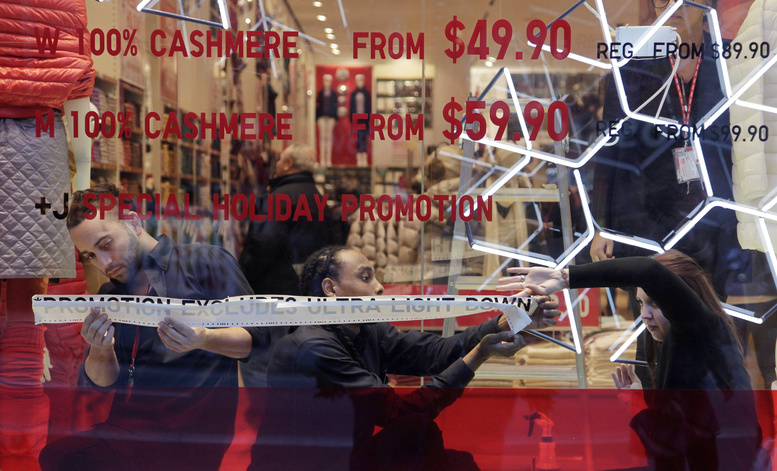 Employees of Uniqlo paste promotional information in a window of the retailer's New York City store. Americans have become increasingly blase about bargains this holiday season.