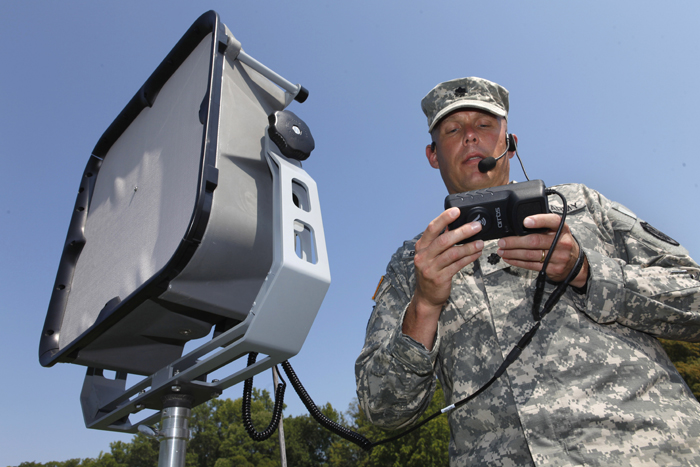 Lt. Col. Jeffrey Bevington, an officer with the Joint Non-Lethal Weapons Directorate, demonstrates one of the military's latest voice projection systems that can project a human voice a mile away and instantly translate from English to another language.