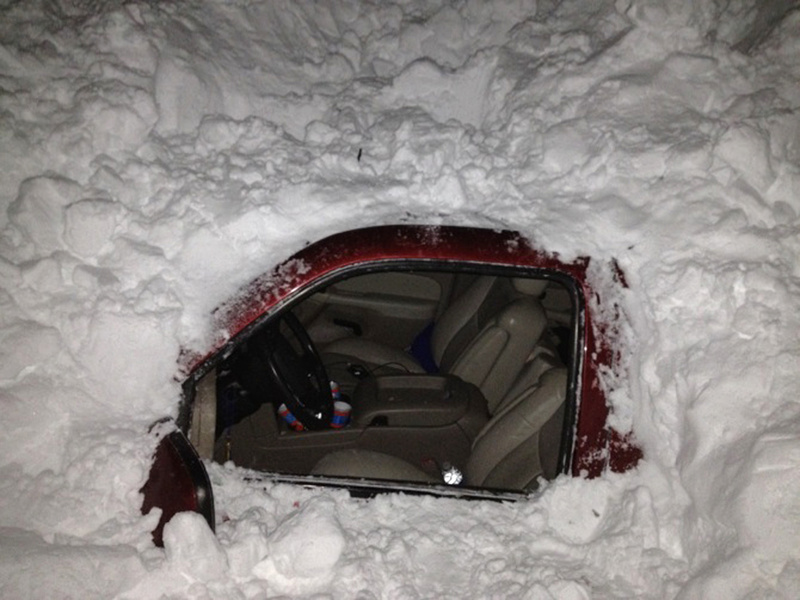 The Higgins family's SUV is shown buried under a snowdrift on U.S. Highway 412 about 30 miles from Clayton, N.M.