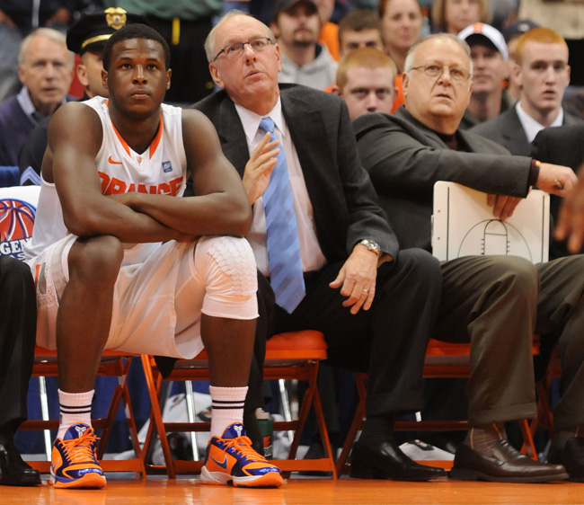 Syracuse basketball player Dion Waiter, left, sits on the bench beside head coach Jim Boeheim, center, and assistant coach Bernie Fine, right, during a game last year.