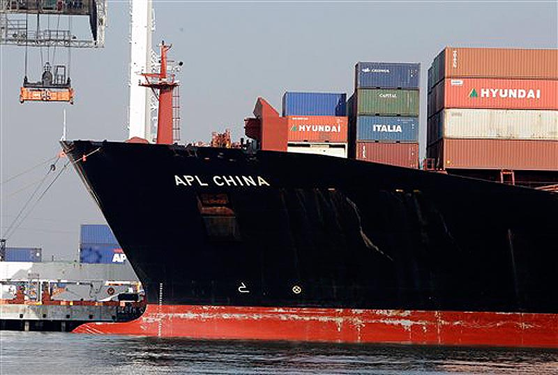 In this Dec. 8, 2011 photo, a container ship is docked at the Port of Oakland in Oakland, Calif. The U.S. trade deficit narrowed in October to its lowest point of the year as Americans bought fewer foreign cars and imported less oil. Exports of American-made autos also fell. (AP Photo/Paul Sakuma)