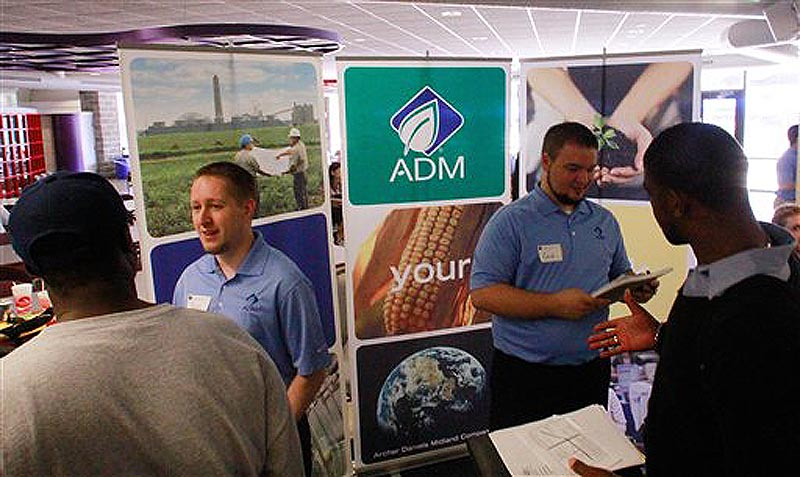 In this Sept. 1, 2011 photo, Archer Daniels Midland Company employees answer questions and hand out job applications during a job fair at the University of Illinois Springfield campus, in Springfield, Ill. The number of people seeking unemployment benefits fell last week to the lowest level in nine months, evidence that the job market is improving. (AP Photo/Seth Perlman) Job Fair