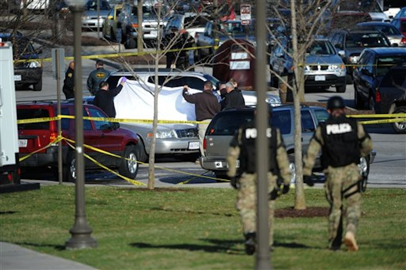 Police officials examine the body of a police officer shot to death in a parking lot on the campus of Virginia Tech, Thursday, Dec. 8, 2011, in Blacksburg, Va. A gunman killed a Virginia Tech police officer Thursday at a campus parking lot and then apparently shot himself to death nearby in a baffling attack that shook up the school nearly five years after it was the scene of the deadliest shooting rampage in modern U.S. history. (AP Photo/Don Petersen)