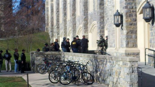 In this image taken on a cell phone, authorities gather outside Torgersen Hall on the Virginia Tech campus in Blacksburg, Va., Thursday, Dec. 8, 2011. A gunman killed a police officer and another person after a traffic stop on the campus Thursday. The school said a police officer pulled someone over for a traffic stop and was shot and killed. The shooter ran toward a nearby parking lot, where a second person was found dead. (AP Photo/The Roanoke Times, Jeff Sturgeon)