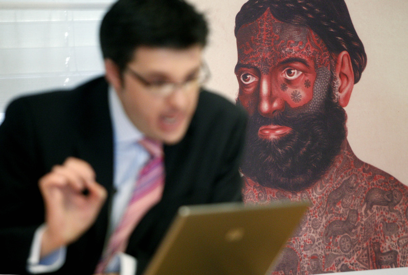 William Purkis, left, of the University of Birmingham discusses tattoos with a picture of a highly tattooed mystic.