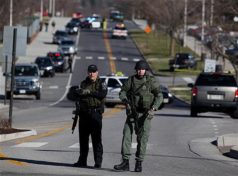 Police officers block a road on the Virginia Tech campus in Blacksburg, Va., after a gunman killed a police officer and another person Thursday, Dec. 8, 2011. The school said a police officer pulled someone over for a traffic stop and was shot and killed. The shooter ran toward a nearby parking lot, where a second person was found dead. (AP Photo/The Roanoke Times, Matt Gentry)