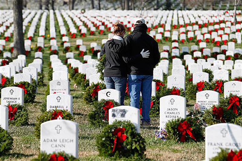 Volunteers pause over the grave of a fallen soldier after laying a holiday wreath during Wreaths Across America Day at Arlington Cemetery today.