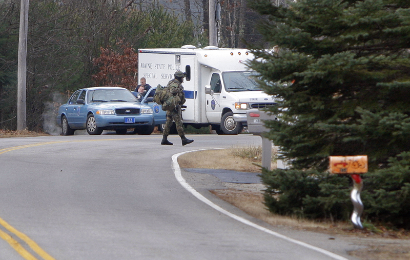A SWAT team member walks across New Dam Road in Sanford this morning. Police are searching for fugitive David Hobson.