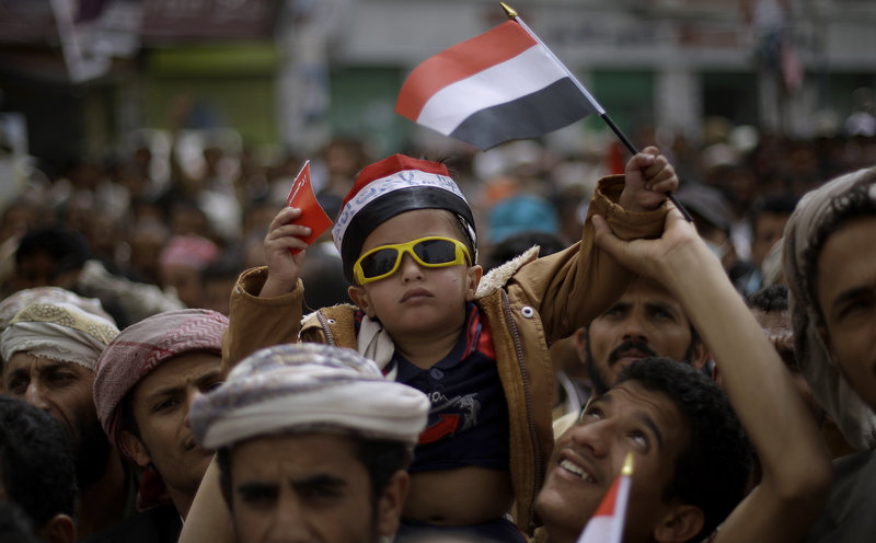 "A Yemeni boy waves his national flag while lifted by anti-government protestors during a demonstration demanding the resignation of Yemeni President Ali Abdullah Saleh, in Sanaa, Yemen, Sunday, March 27, 2011. ""The Protestor"" was named Time's ""Person of the Year"". (AP Photo/Muhammed Muheisen)"