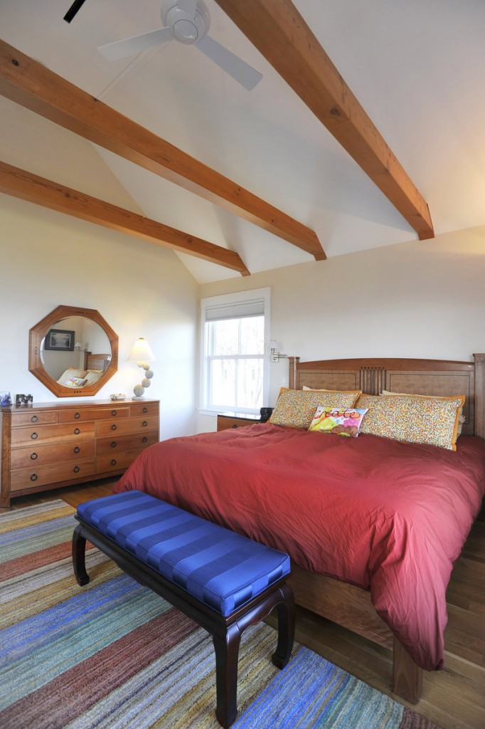 Wood beams and colorful accents stand out in the master bedroom.