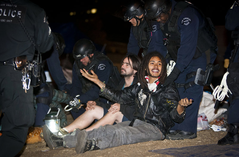 Police arrest a member of Occupy Philly, Wednesday, in Philadelphia, after a small group refused to clear a street while police and other officials pulled down tents to clear out the encampment in Dilworth Plaza.