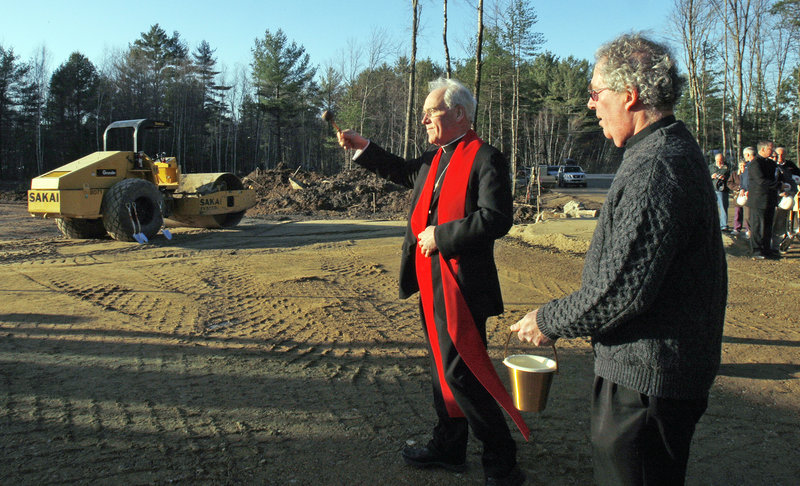 Bishop Richard Malone sprinkles holy water at the site of a new Roman Catholic church in South Berwick on Wednesday. At right is the Rev. Joseph Cahill, the parochial vicar for the parish.