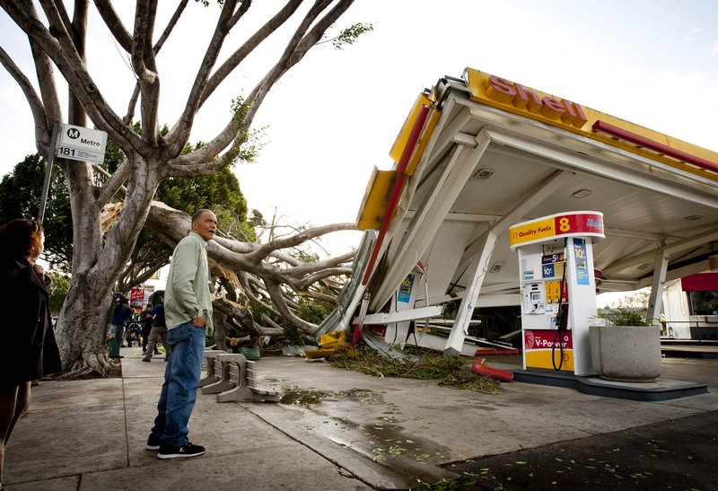 Keith Curo of Pasadena, Calif., stops to look over the damage caused by a fallen tree at a Shell gas station Thursday, as some of the worst winds in years blasted California overnight.
