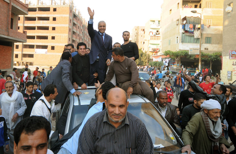 Supporters of Mustafa Bakri center, surround his car as they celebrate after he won a seat in the first round in South Cairo's Helwan district, Egypt, Thursday.