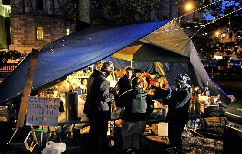 Occupy Maine members gather around the kitchen area of the Lincoln Park encampment last month.