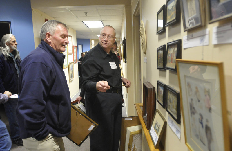 "Bob Parker, of Goodwill Industries of Northern New England, talks with Pete Cloutier, left, of South Portland, about the art for sale during Goodwill's sixth biannual ""Art for Everyone: A Collection of Donated Art"" on Friday."