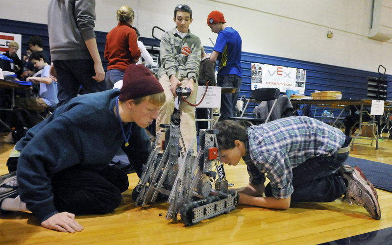 Harry Munroe, left, and Braden Becker, right, inspect their team's robot as teammate Carter Hall, center, operates the controls before the Yarmouth team's next competition during the Southern Maine VEX Tournament on Saturday in Gorham.
